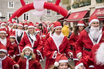 Festival-goers running through the town during the Santa Fun Run at the Padstow Christmas Festival.